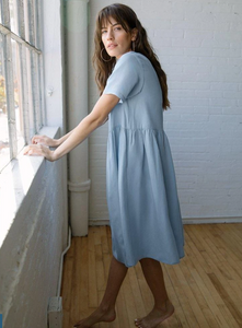 A woman with brown hair and large hoop earrings stands barefoot by a window wearing a light blue midi dress.