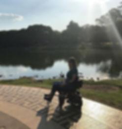 Ketly sentanda na sua cadeira olhando para frente e atrás o lago do Ibirapuera