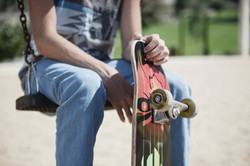 man sitting down holding a skateboard