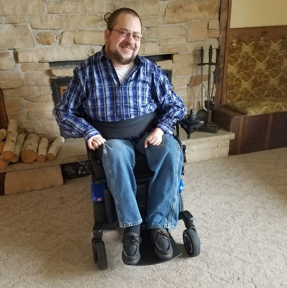 Image of a middle aged white male with dark hair, goatee, beard, wearing glasses and smiling while sitting in a power wheelchair in front of a fireplace.