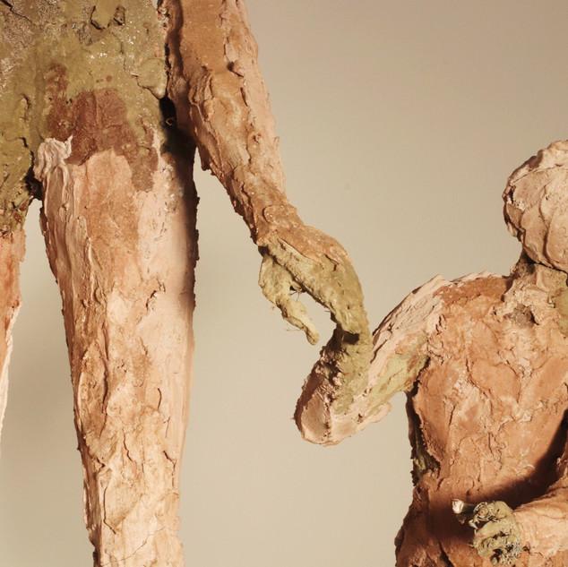 Folk art sculptue of woman and child.