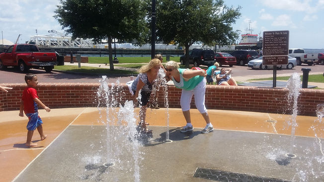 Family playing in fountain during scavenger hunt adventure downtown Pensacola, FL