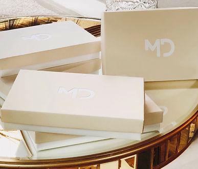 Foto com caixas brancas, com tampa rosa e logo da marca na tampa que é rosa claro.