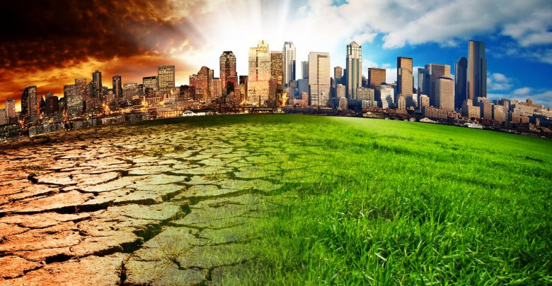 City skyline with one side having green grass and blue sky and the other with dry cracked ground
