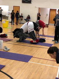 AJ the Bronc and other students practicing yoga on Earth Day 2018
