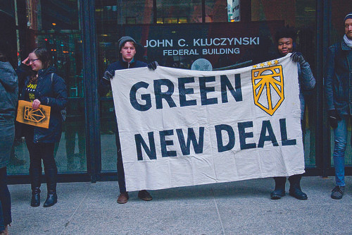 Two students hold Green New Deal banner at a protest