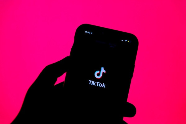 The tik tok logo on a phone with a pink background
