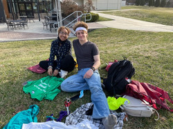 Green Team Members sitting on the campus lawn making upcycled crafts