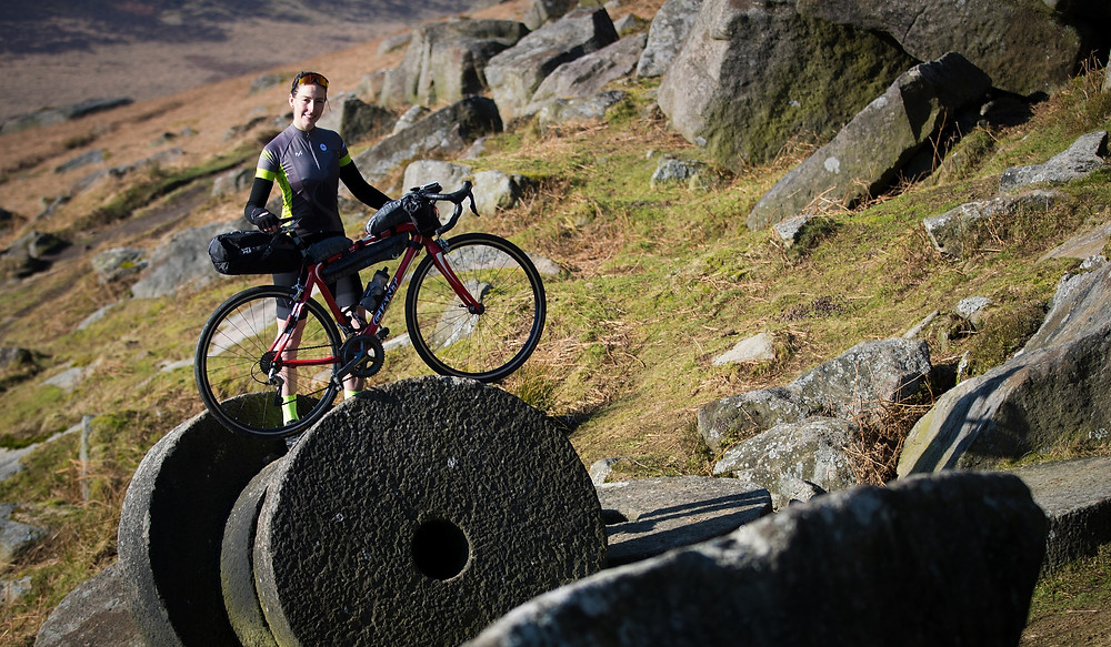 Lorna Fisher with her bike on a Peak District mill stone