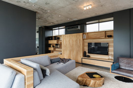 Modern Living Room with wooden custom shelving and slate blue walls