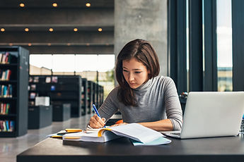 Female-student-taking-notes-from-a-book-at-library.-Young-asian-woman-sitting-at-table-doi