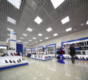 Inside spacious lighting shoes shop with models on white shelves