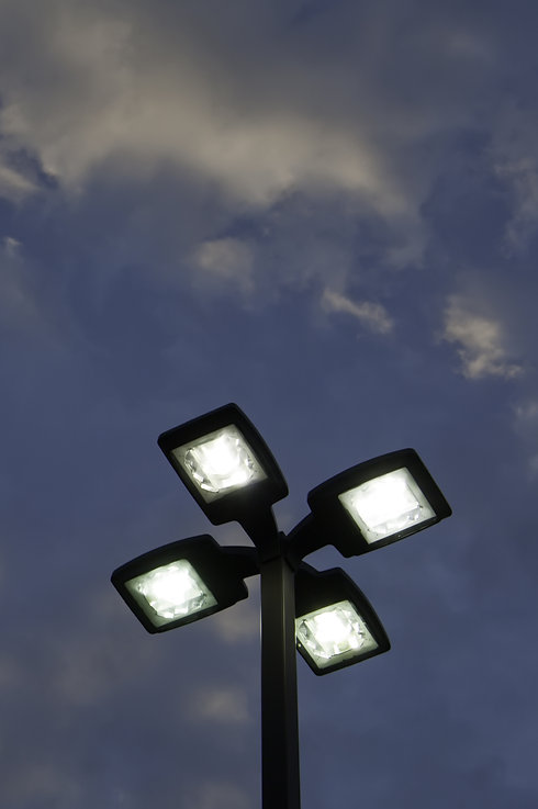 Top of outdoor lightpole with four electric lights against evening sky