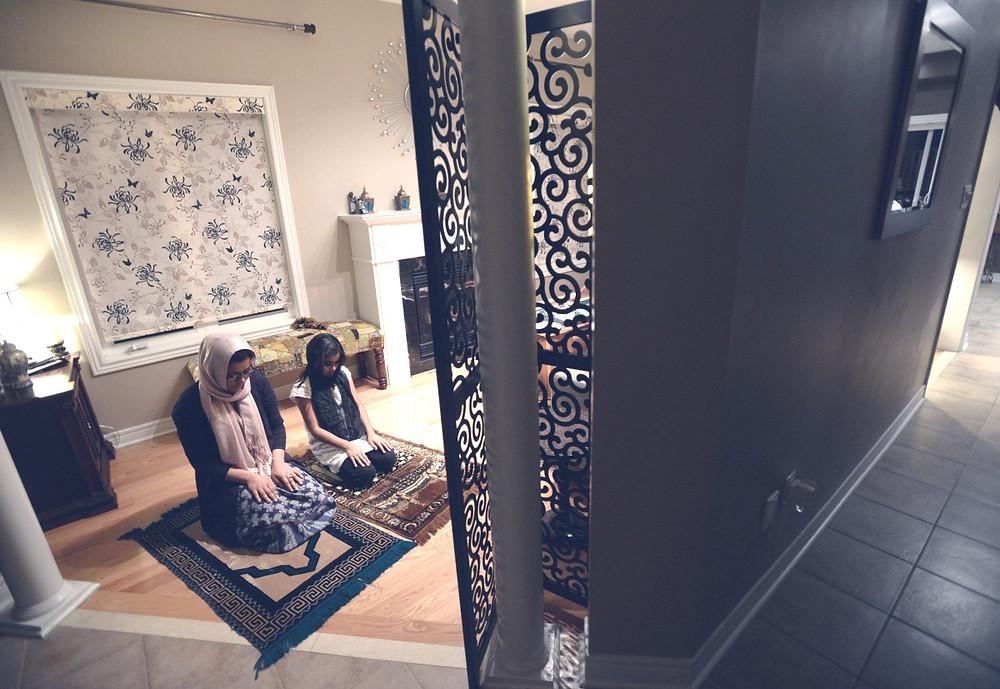 Family praying at home during Ramadan Night prayer, taraweeh