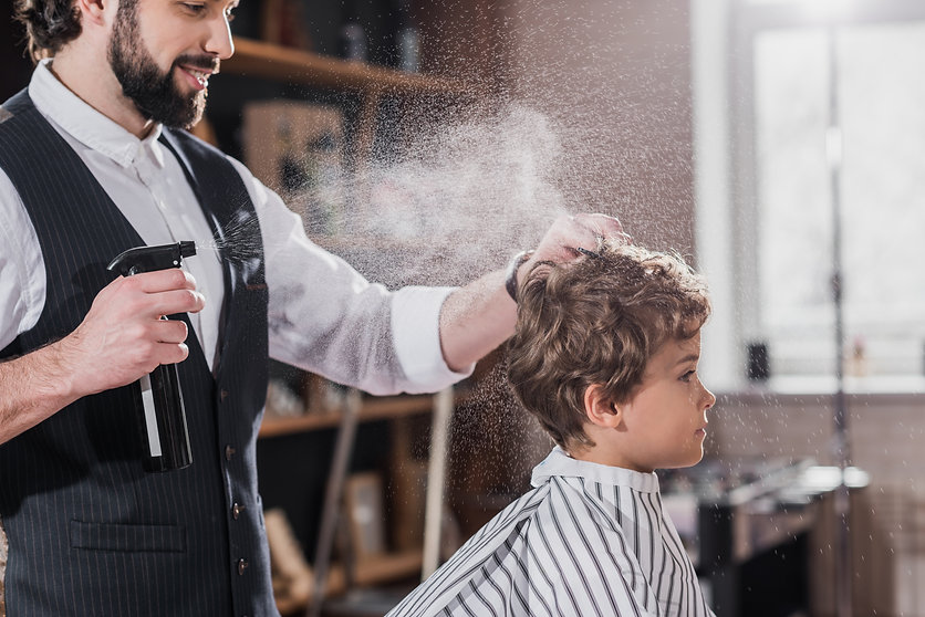 smiling bearded barber combing and spray