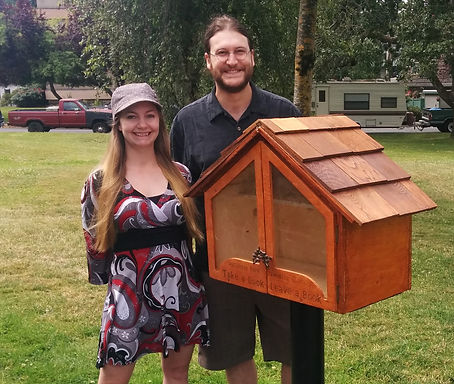 Teale Phelps Bondaroff and his partner Stephanie Ferguson wih the little free library they curate in Rutledge Park, Saanich