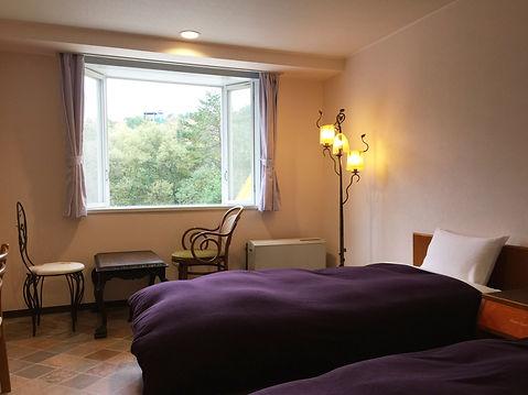 浅間高原ホテルのツインベッドルーム,緑豊かな森を望む窓