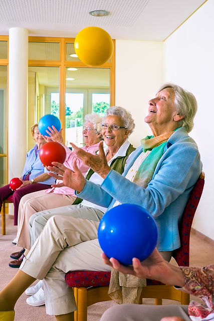 Group of happy elderly ladies in a seniors gym doing hand coordination exercises throwing