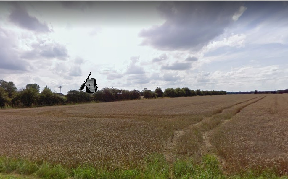 Field with distant windmill
