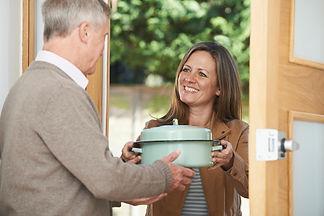 Woman-Bringing-Meal-For-Elderly-Neighbou