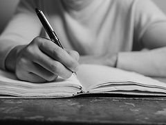 a hand holding a pen writing in a notebook