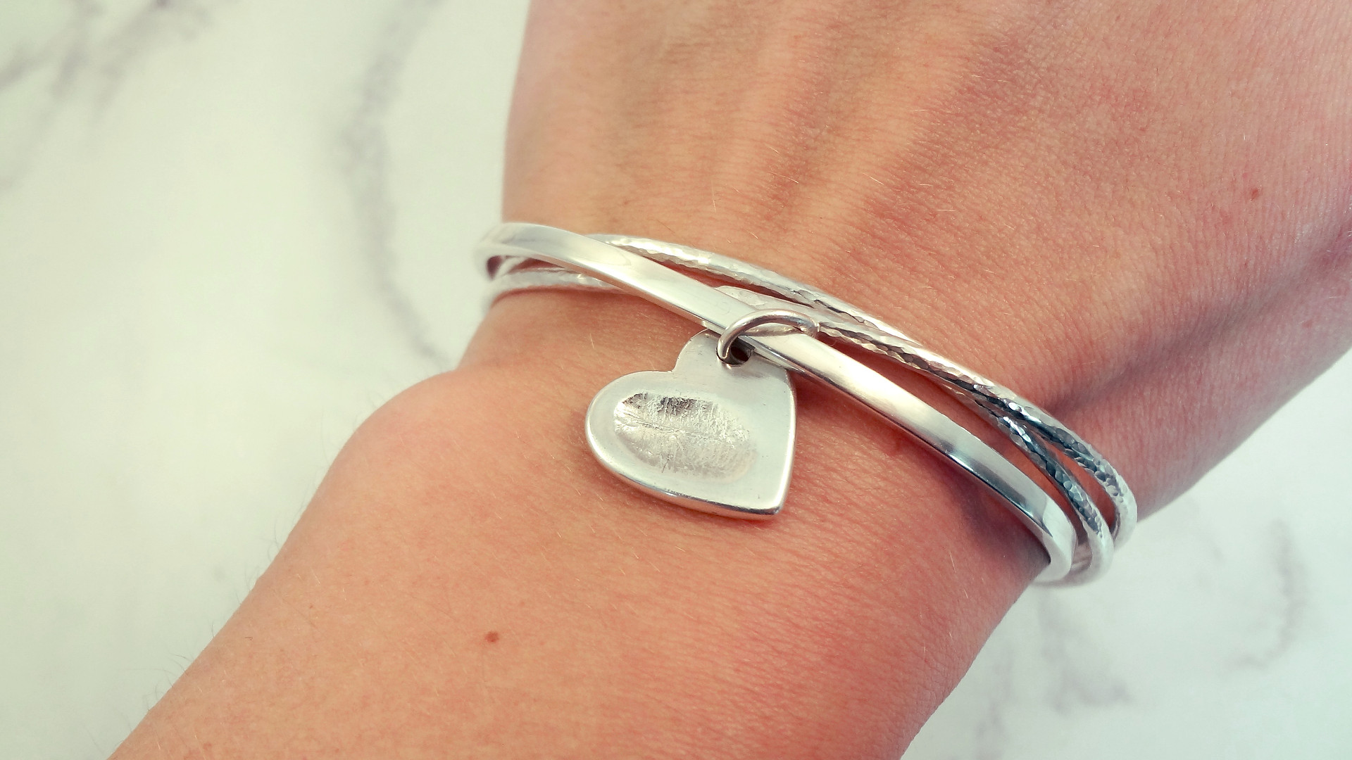 Fingerprint charm on an entwined bangle set
