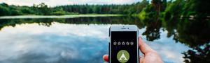 Smartphone mit Bewertungs-Sternen an einem See auf einem Campingplatz