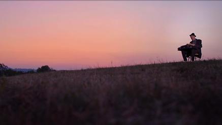 Aufnahme des Protagonisten auf einer Wiese mit Sonnenuntergang im Hintergrund für die Fernsehsendung Vogelwild
