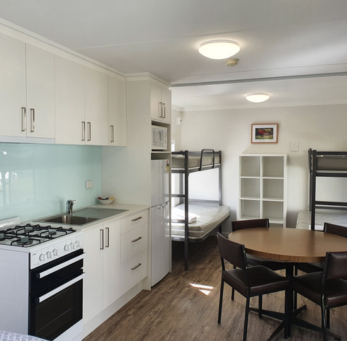 Kitchen dinning area and bunk beds riverfront cabin accommodation