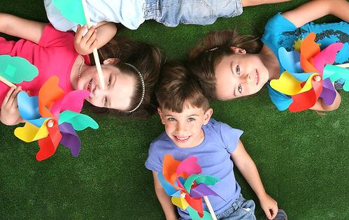 Children smiling nd playing with pinwheels