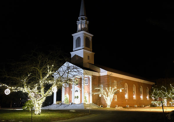 Front view of the Brookside Church wth holiday lights at nigh
