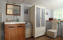 Ванная комната в пастельных тонах с отделкой имимтацией бруса в деревянном доме