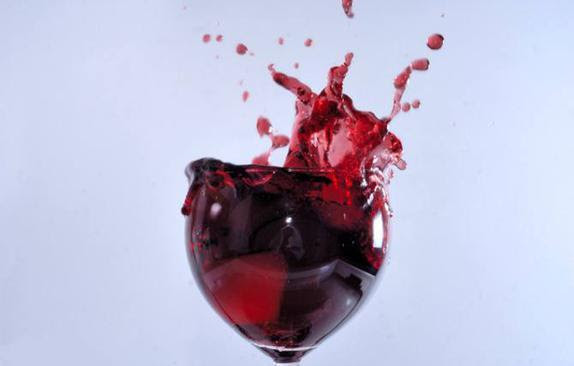 Red wine splashing in glass
