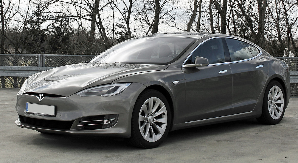 Tesla Model S vehicle on the side of a street with a wilderness backdrop