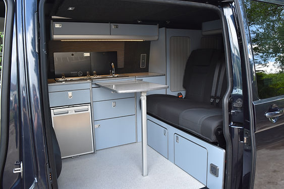 Camper conversion with lazuli unite and sparkle gloss white worktop with a rear overbed locker for storage at Apple County Customs Bristol