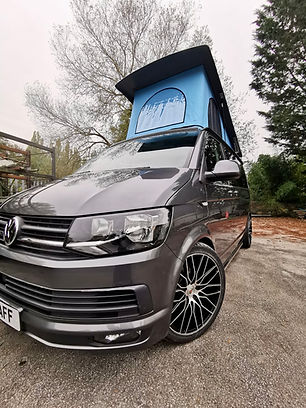 Grey Volkswagen Transporter with Skyline pop top roof and bay blue canvas