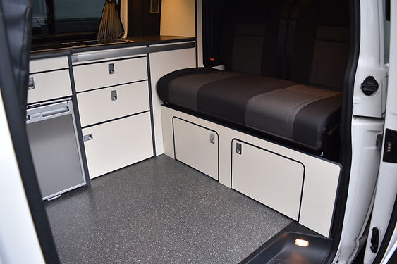 VW camper conversion interior with cream units and brushed metal work tops and a rear overbed locker at Apple County Customs Bristol