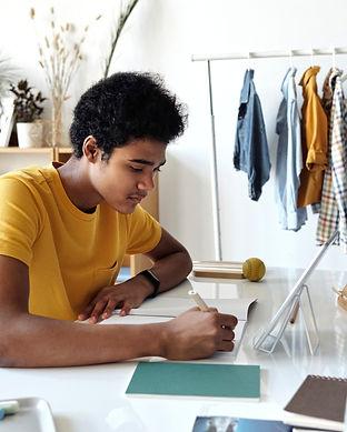 boy-wearing-yellow-shirt-while-writing-o
