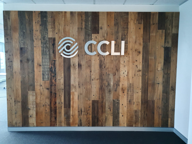 7. This rustic pine reclaimed timber feature wall sets off the customer's silver signage and logo.
