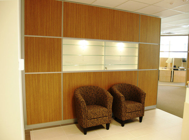 2. A modern classic touch is created through the use of Zebrano laminex panels offset with aluminium inserts and skirting. A product display case adds the focal point.