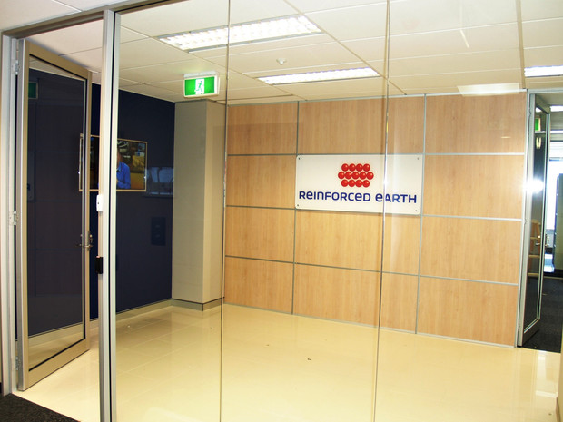 9. Laminated panelling with 25mm silver strips inlays and centered perspex company signage with round silver spacers.