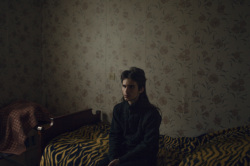 """Anatoly, 23 years old, poses for a portrait at his apartment in St. Petersburg, Russia.   Anatoly says: """"I've been walking alone since I was 7. There is a river called Volkovka near my house where the railroad and garages are. Before there were thickets instead of garages and I just went to these thickets until the end of the day. There were no people, people are an aggression."""""""