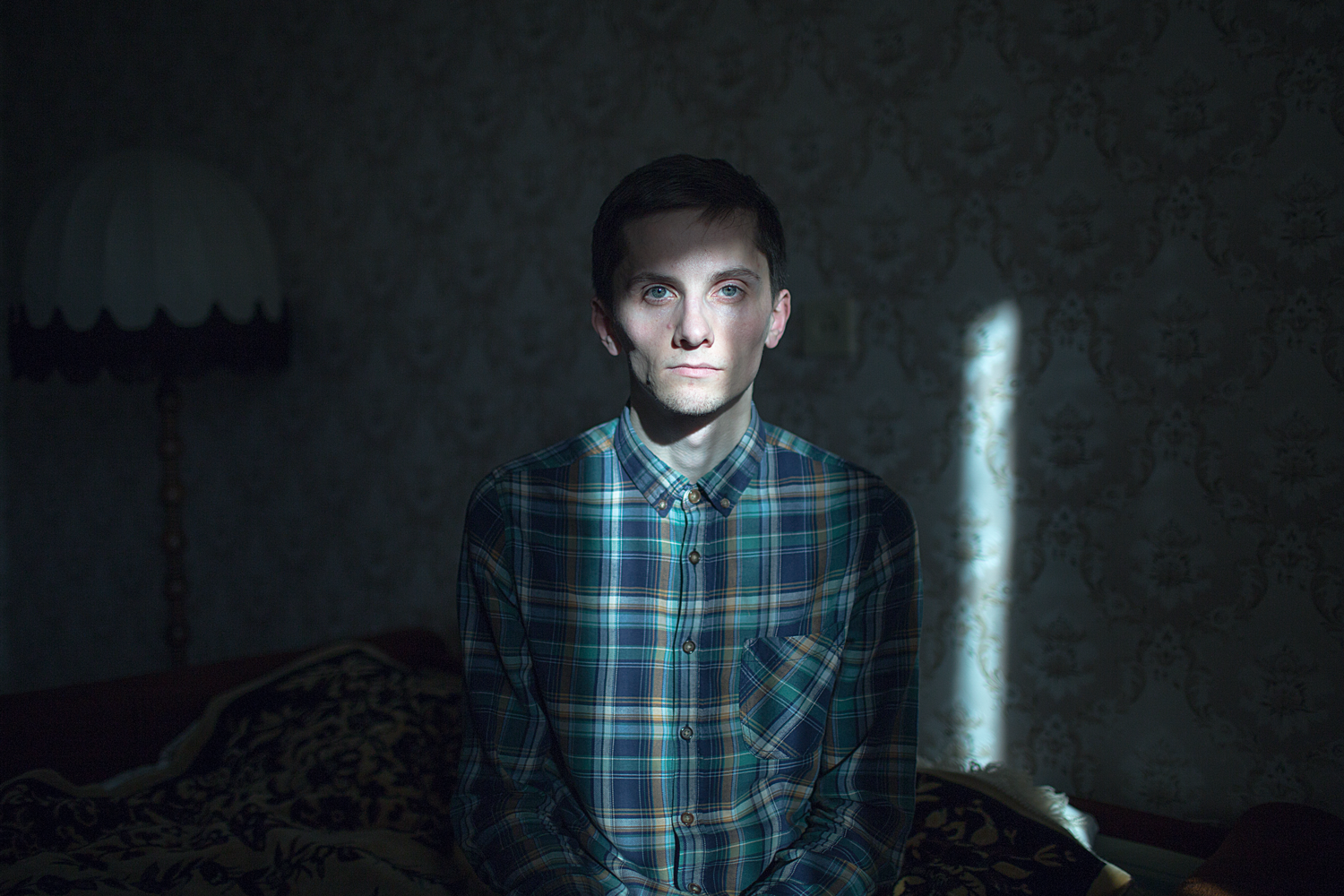 """Oleg, 27 years old, poses for a portrait at his apartment in St. Petersburg, Russia.    Oleg says: """"When it came to kissing a girl, I started laughing."""""""