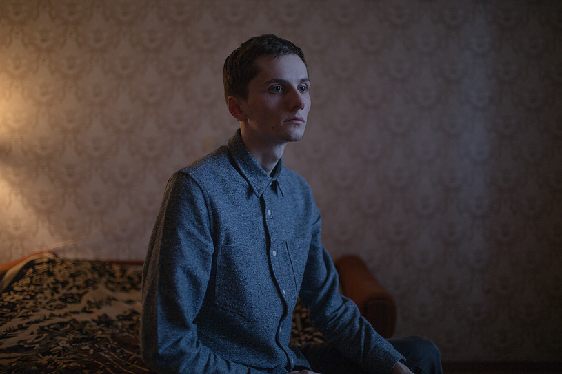 """Oleg, 27 years old, poses for a portrait at his apartment in St. Petersburg, Russia.    Oleg says: """"Remember the magazine Rovesnik? Every month me and my mom went to Soyuzpechat* kiosk. And once Brad Pitt was on the cover. Actually, I don't like Brad Pitt... Anyway, mom bought me the magazine, and I took and kissed the cover for some reason. I can't explain why I did it. But mom was perplexed."""" *Soyuzpechat is a network of press kiosks existing in USSR."""