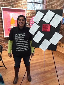Kai Coggin stands in front of her poems that she created during the POETRY TALKS BACK event.