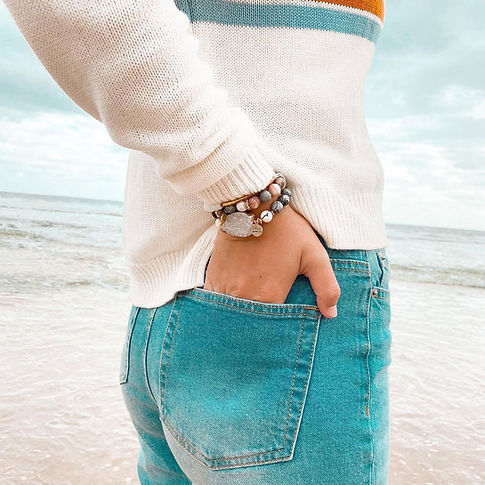 woman wearing turquoise pants on the beach with stacked bracelet collection on her right wrist
