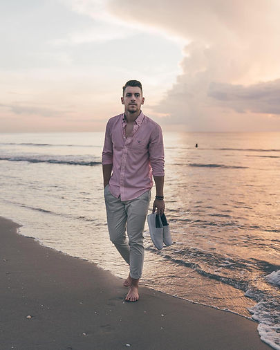 man strolling barefoot on beach holding his sneakers and wearing the Muze collection bracelets