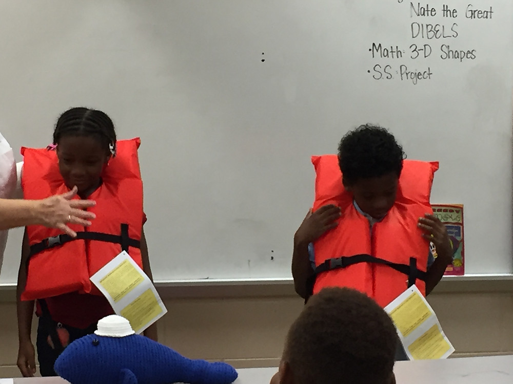 Students wearing life vests learning about water safety.