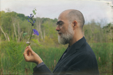 Fredo Viola, hatless holding flower, portrait by Nicholas Kahn