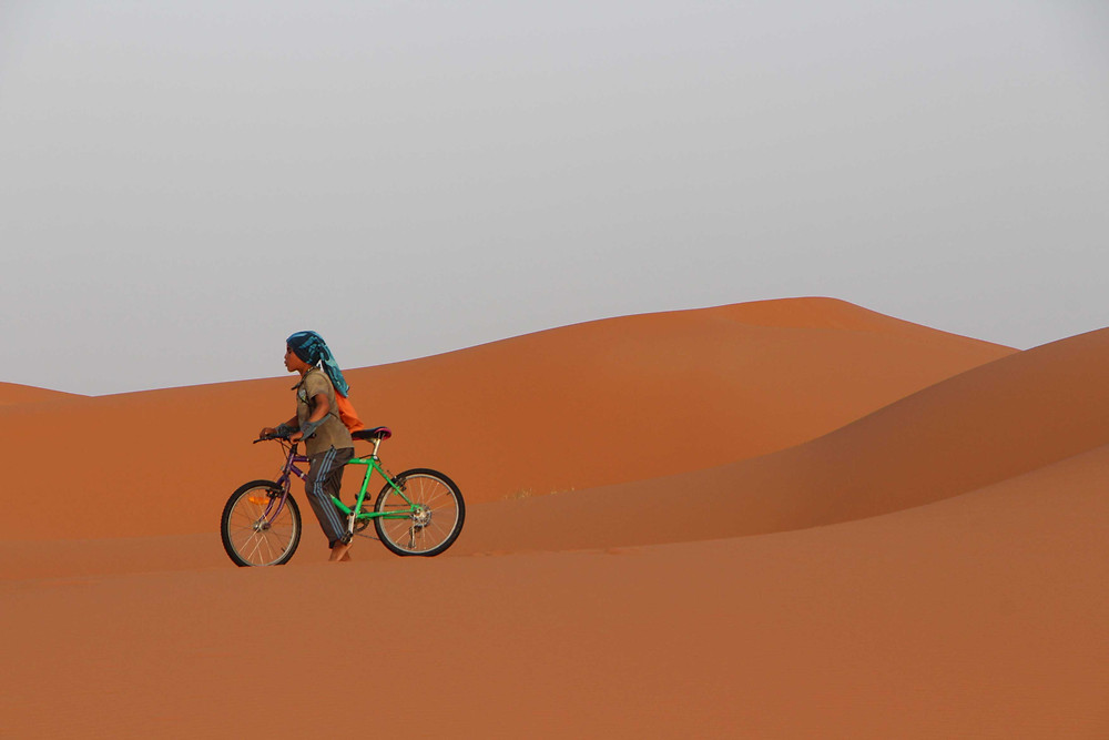 A nomad child cycles on the sund dunes